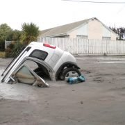 A car in a hole caused by liquefaction following the Christchurch earthquake